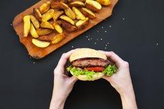 Руки держа свежий бургер Зажаренные картошки на деревянной доске стоковые изображения rf