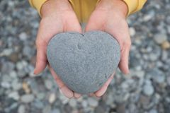 Руки держа сердце/камень сердца форменный Стоковые Изображения