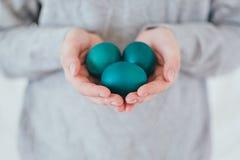 Руки держа современные пасхальные яйца покрашенный в зеленом цвете стоковое изображение rf