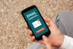 Руки держа умный телефон с концепцией маркетинга электронной почты на экране Стоковые Изображения