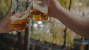 2 руки держа чашки прозрачной пластмассы с светлым пивом и приветственными восклицаниями с ними акции видеоматериалы