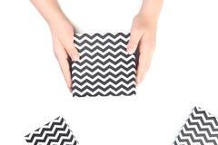 Руки держа черно-белые подарочные коробки шеврона стоковое изображение