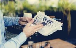 Руки держа чтение газеты на кафе стоковая фотография rf
