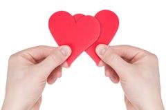 Руки держа 2 красных бумажных сердца Стоковые Фотографии RF