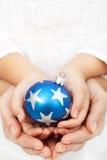 Руки держа bauble рождества стоковое изображение