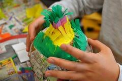 Руки детей делают pinata стоковое фото
