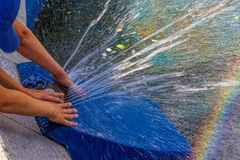 Руки детей играют с двигателем фонтана стоковые изображения
