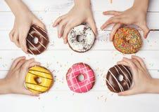 Руки детей принимают отсутствующие красочные donuts стоковое фото