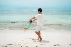Руки дочери удерживания отца при игре качания вращают на пляже стоковые фотографии rf