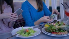 Руки друзей женщин используя мобильный телефон для фото красивого салата во время здорового обедающего во время диеты для потери  сток-видео