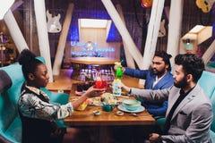 Руки друзей совместно в круге держа различные коктейли с льдом на предпосылке старого деревянного стола стоковое изображение