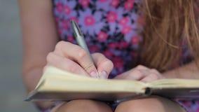 Руки девушек с сочинительством ручки на тетради с прописями акции видеоматериалы