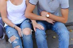 Руки девушка и мальчик соединяют сидеть на крылечке ресторана Стоковое фото RF