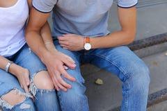 Руки девушка и мальчик соединяют сидеть на крылечке ресторана Стоковая Фотография RF