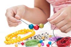 Руки девушки отбортовывая ожерелье Стоковые Фото