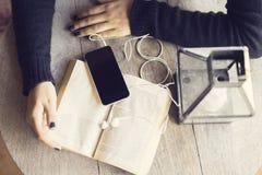 Руки девушки с книгой и smartphone с наушниками Стоковое Изображение RF