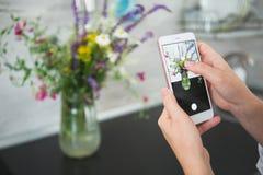 Руки девушки фотографируя букет цветков Стоковые Изображения RF