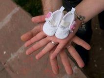 Руки держа ботинки младенца ждать младенца Беременность Стоковые Фото