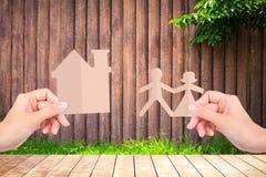 Руки держа бумаги семьи на деревянной предпосылке загородки Стоковое Фото
