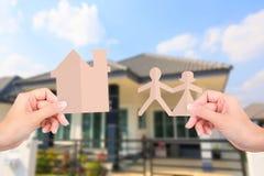 Руки держа бумаги семьи на домашней предпосылке Стоковая Фотография