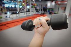 Руки держа гантели в спортивном клубе или спортзале и фитнесе Стоковое Фото