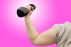 Руки держа гантели в спортивном клубе на розовой предпосылке Стоковая Фотография