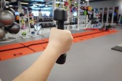 Руки держа гантели в спортивном клубе Стоковое Изображение
