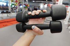 Руки держа гантели в спортивном клубе Стоковые Фотографии RF