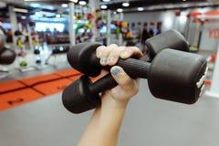 Руки держа гантели в спортивном клубе Стоковая Фотография