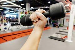 Руки держа гантели в спортивном клубе Стоковое фото RF