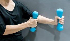 Руки держа голубые гантели Стоковое фото RF