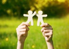 Руки держа деревянных маленьких людей Стоковые Фото