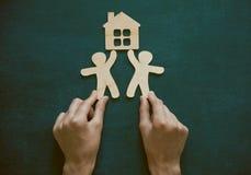 Руки держа деревянных людей и дома Стоковые Изображения RF