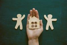 Руки держа деревянных людей и дома Стоковое Фото
