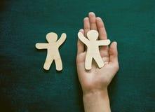Руки держа деревянных людей Стоковая Фотография