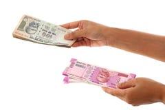 Руки держа индейца 2000 и 100 примечаний рупии Стоковое Изображение RF