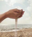 Руки держа и разливая зашкурят с пляжем на заднем плане стоковые фотографии rf