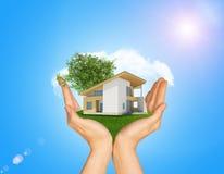 Руки держа коттедж на зеленой траве Справочная информация Стоковые Фото