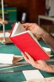 Руки держа красную книгу крышки на таблице стоковое фото