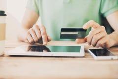 Руки держа кредитную карточку и используя цифровую таблетку Он-лайн принципиальная схема покупкы Стоковые Изображения RF