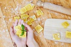 Руки держа макаронные изделия равиоли Стоковые Изображения