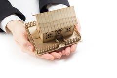 Руки держа маленькую модель дома имущество принципиальной схемы реальное Стоковое Фото