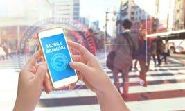 Руки держа мобильный телефон с передвижным банком Стоковые Изображения RF