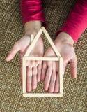 Руки держа модельный дом сделанный из деревянных ручек Стоковое Фото