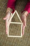 Руки держа модельный дом сделанный из деревянных ручек Стоковые Фото