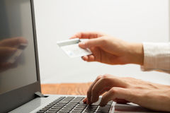 Руки держа номера кредитной карточки печатая на ПК таблетки делая онлайн оплатой дома деревянный стол прочешите покупка руки фоку Стоковое Фото