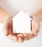 Руки держа дом белой бумаги Стоковая Фотография