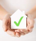 Руки держа дом с контрольной пометкой Стоковое Фото