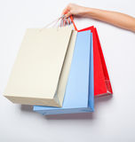 Руки держа покрашенные хозяйственные сумки на белой предпосылке Стоковая Фотография