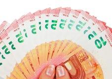 2 руки держа 10 примечаний евро на белизне Стоковая Фотография
